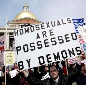 "Gay marriage opponent Leonard Gendron, a local pastor, holds a sign reading ""Homosexuals are Possessed by Demons"" outside the Massachusetts State House in Boston March 11, 2004 where the Massachusetts Legislature is debating an amendment to the state's constitution banning gay marriage.  On November 11, 2003 the Massachusetts Supreme Judicial Court ruled that the state must issue marriage licenses to gay couples.       REUTERS/Brian Snyder"